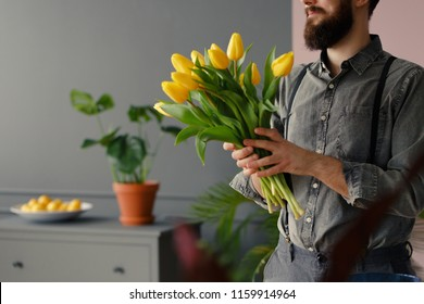 Man in grey shirt and with beard holding bouquet of yellow tulips