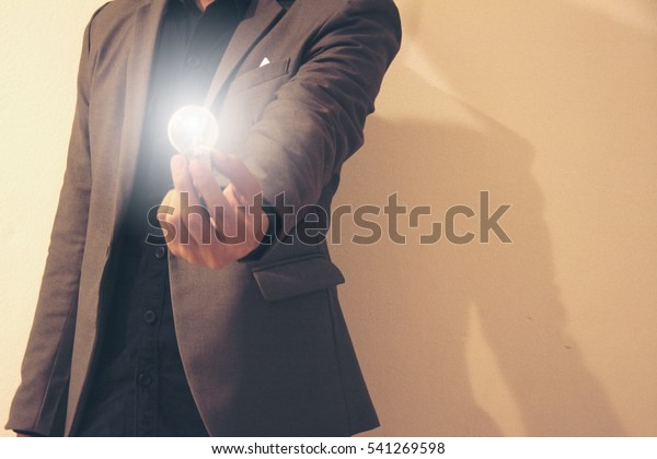 Man in grey suit hold light in left hand.This picture is a concept to mean thinking.