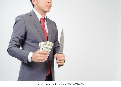 Man in grey suit holding knife and dollar note