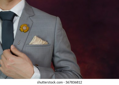Man in grey suit, plaid texture, blue necktie, flower brooch, and dot pattern handkerchief, close up