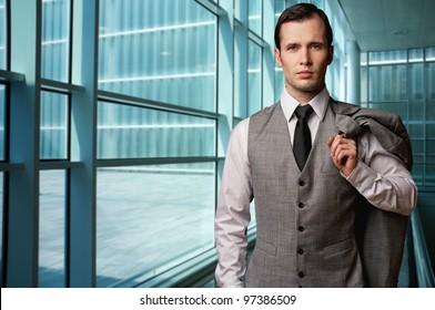 Man in grey suite in modern building.
