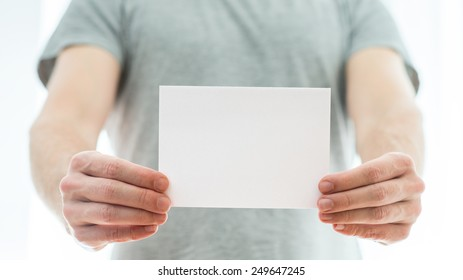 Man in a grey t-shirt holding a blank white card in his extended hands with copyspace for your text or advertisement.