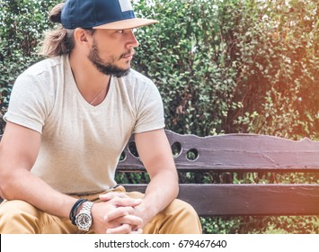 Man in grey tshirt and yellow jeans sitting on the bench outdoors, horizontal Mockup