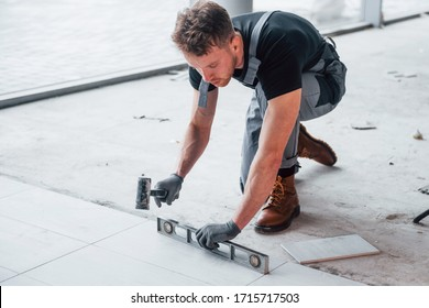 Man in grey uniform installing plate indoors in modern big office at daytime.