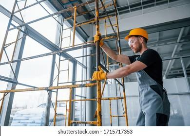 Der Mensch in grauer Uniform arbeitet tagsüber mit dem Bau von Innenräumen im modernen Großbüro.
