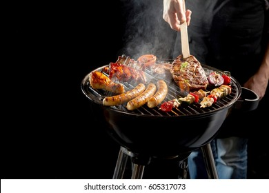 Man grilling an assortment of meat and kebabs on a portable barbecue lifting a t-bone steak with a pair of tongs in a close up view of his hand