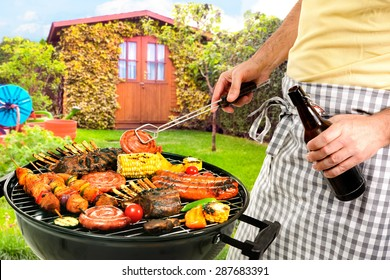 Man grilling meat on barbecue in front of backyard