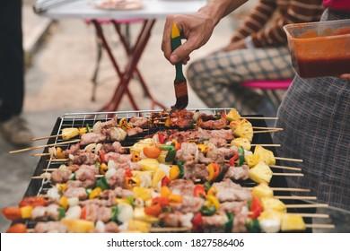 Ein Mann grillt Schweinefleisch und Grill auf der Abendparty. Essen, Menschen und Familienzeitkonzept.