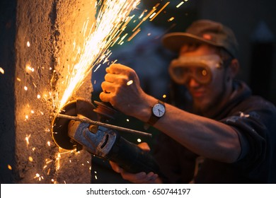 Man with a grinder is building a fence from wood and concrete at outdoor. Bright sparks are flying from cutting metal abrasive disk of the angle grinder.