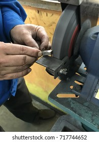 A man grinding a tool bit by using a grinding machine