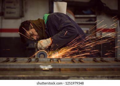 Man grinding in workshop, with protection equipment