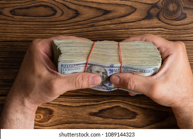 Man gripping a thick stack of 100 dollar bills or Benjies tightly between his fingers over a wooden table in a conceptual overhead image