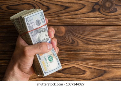 Man gripping a thick stack of 100 dollar bills or Benjamins in his hand over a rustic wood background with copy space