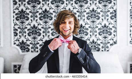 Man the groom in a wedding formal costume with butterfly. Suit, Hands, care, tie, to correct, to adjust, fashion, bow. Instagram colors toning