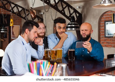 Man Group In Bar Drinking Beer, Frustrated Guy Hold Cell Smart Phone, Mix Race Friends Upset Serious Looking