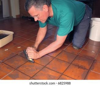 Man grouting ceramic tile