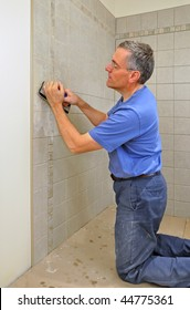 Man grouting ceramic tiles in bathroom
