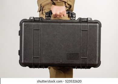 man or guard hand holding case with weapon isolated at white background. Military and security concept.