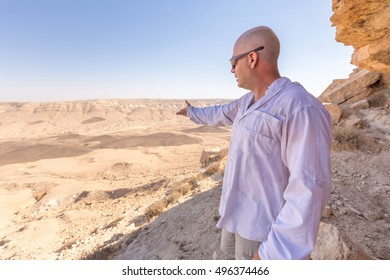 Man guide showing explaining geologist pointing hand viewing desert landscape rock formations stone cliff edge, Middle East scenic .