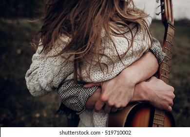 man with guitar hugging his boho gypsy woman closeup in windy field. atmospheric sensual moment. stylish hipster couple in fashionable look. rustic wedding concept