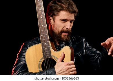 man with a guitar on a dark background, musician