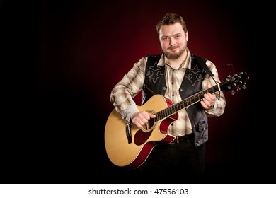 man with a guitar on a dark red background