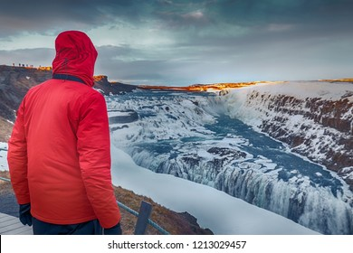 Man at Gullfoss waterfall Iceland with snow in winter. Dramatic landscape of this majestic waterfall in the Icelandic Golden circle. Travel and nature concepts.