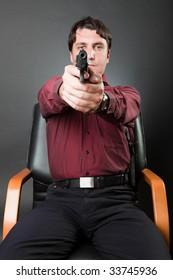 Man with a gun against a dark background