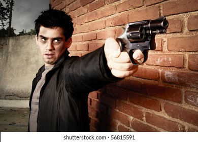 man with gun besides a brick wall