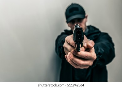 Man with the gun in dark clothes. Preparation for storm of the room. Robbery crime. Grange photo style.