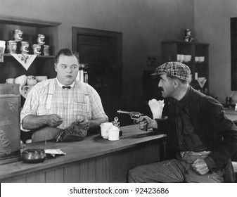 Man with a gun holding up a diner owner
