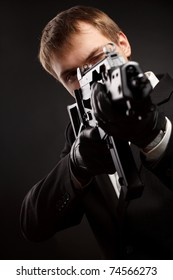Man with gun over gradient gray. Focused on head