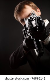 Man with gun over gradient gray. Focused on aim.