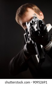 Man with gun over gradient gray. Focused on gun.