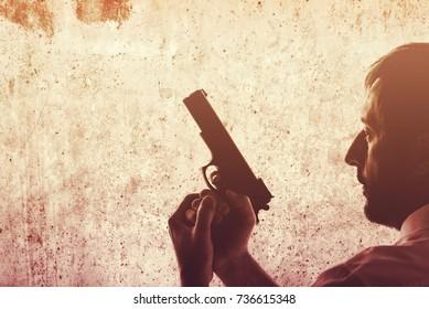 Man with a gun. Police officer, criminal investigation detective or secret service agent. Grunge edit.