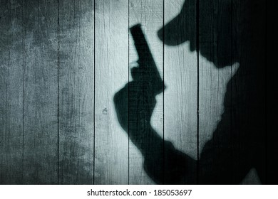 Man with a gun in shadow on a wooden background. You can see more silhouettes and shadows on my page.