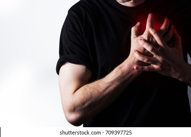 man, guy in a black t shirt on a white background hold hands on his heart, heart atack, severe heartache, chest  myocardial infarction