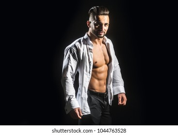 Man. Guy in a white shirt on a black background. Young businessman with a stylish hairstyle. Male model. Athlete from a beautiful strong body in an informal setting. Beautiful young man's face
