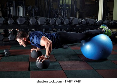 Man at the gym doing exercises for his abs with a Swiss ball.Low light.