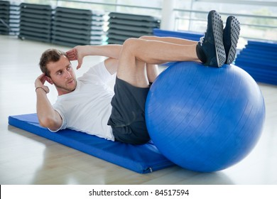 Man at the gym doing exercises for his abs with a Swiss ball