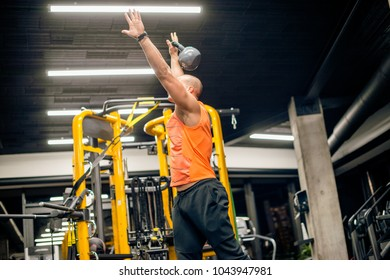 Man in gym is doing swing exercise with kettlebell