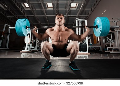 Man at the gym. Execute exercise squatting with weight, in gym