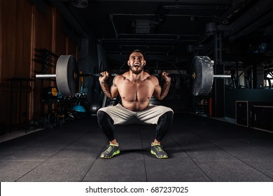 Man at the gym executing exercise squatting with weight