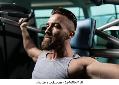 Man In The Gym Exercising On His Shoulders On Machine With Cable In The Gym