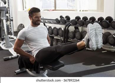 Man in gym, leg raise, abdominal muscles