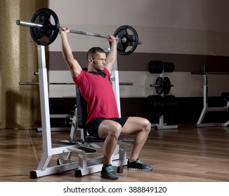 man at the gym makes exercises with barbell