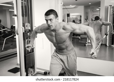 Man at the gym. Man makes exercises. Sport, power, dumbbells, tension, exercise - the concept of a healthy lifestyle. Article about fitness and sports.
