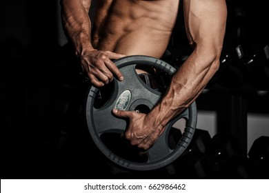 man in gym. Muscular bodybuilder guy doing exercises with barbell. Strong person with Tense strong male hand with veins barbell.