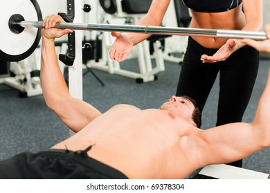man in gym with personal fitness trainer exercising power gymnastics with a barbell