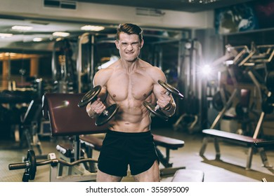 man in the gym training with dumbbells